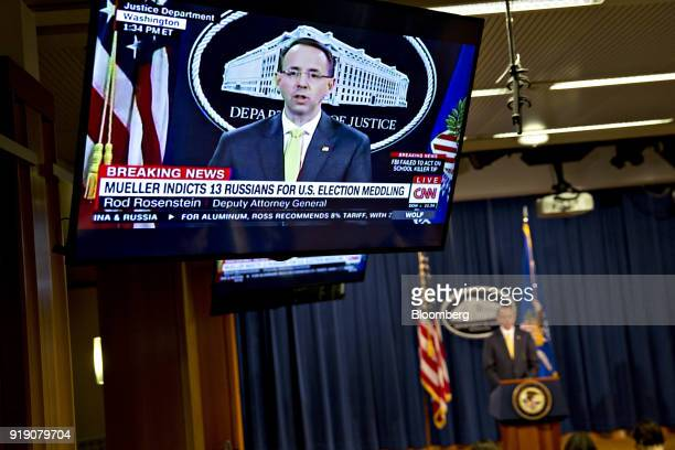 A television displays Rod Rosenstein deputy attorney general speaking during a news conference at the Department of Justice in Washington DC US on...