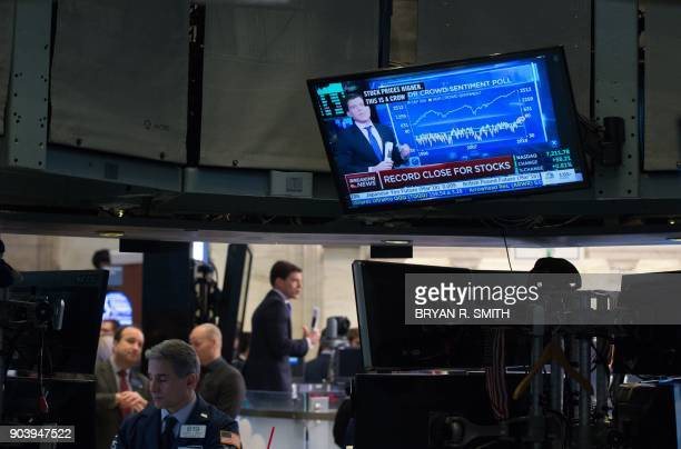 A television displays the closing numbers after the closing bell of the Dow Industrial Average at the New York Stock Exchange on January 11 2018 in...