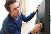 Television Engineer Installing New TV At Home