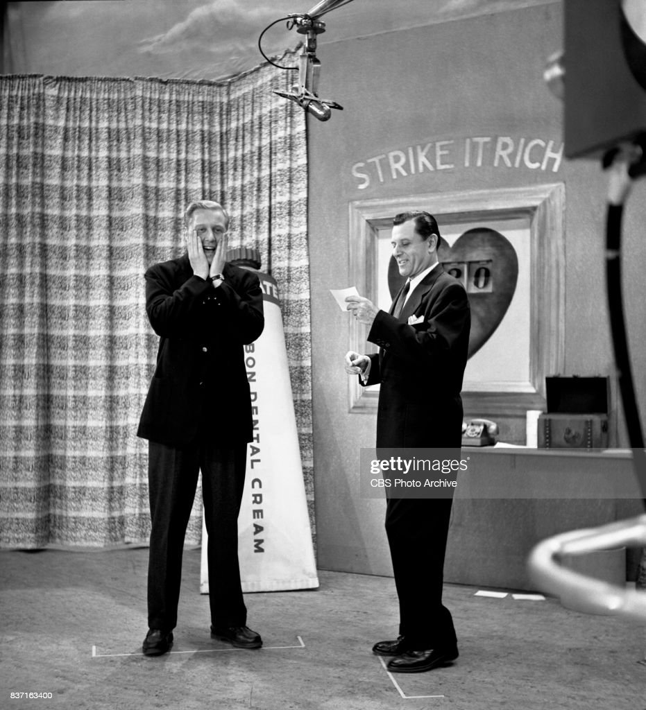 CBS television game show Strike It Rich with host Warren Hull (at right) with George Gaynes (star of Wonderful Town). Image dated April 17, 1953. New York, NY.