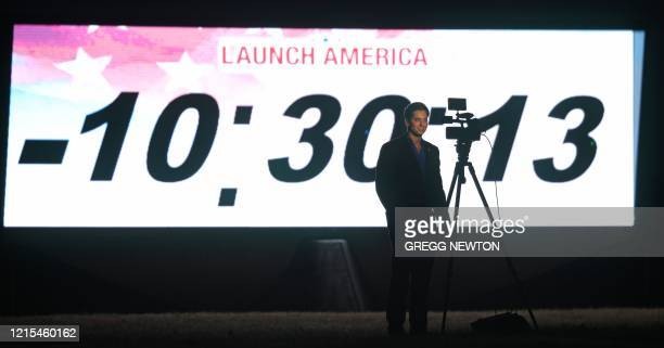 A television journalist broadcasts in front of the countdown clock shortly before sunrise on launch day at the Kennedy Space Center in Florida on May...