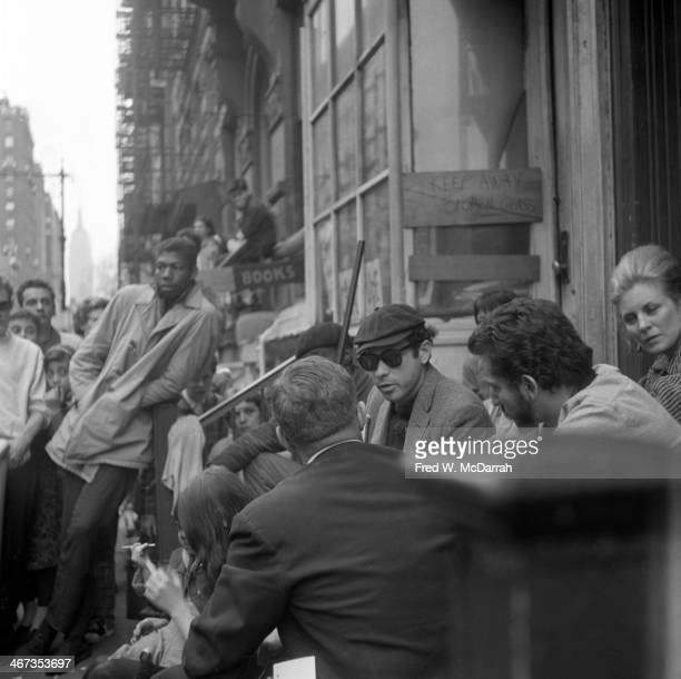 Television journalist Danny Meenan interviews photographer Fred W McDarrah and unidentified others on a stoop on MacDougal Street New York New York...