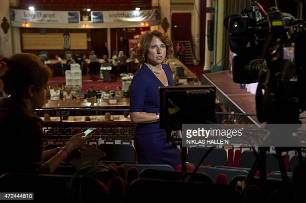 A television journalist prepares to go onair as counting staff await the arrival of the first ballot boxes at the counting centre in Margate...