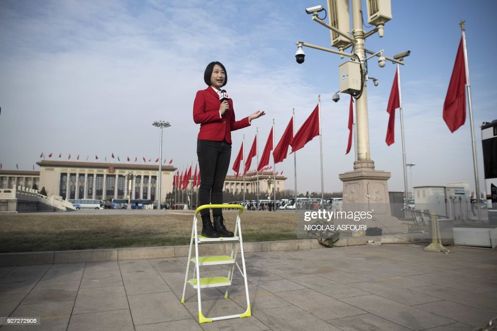 TOPSHOT - A television journalist reports live ahead of the opening session of the National People's Congress, China's legislature, in Beijing's Great Hall of the People on March 5, 2018. China's rubber-stamp parliament opens a major annual session set to expand President Xi Jinping's considerable power and clear him a path towards lifelong rule. /