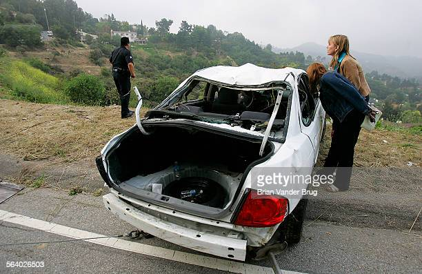 Television journalists look inside a car where eight Orange County teenagers were injured when their Nissan Sentra plunged nearly 250 feet over a...