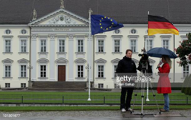 Television journalists stand outside Bellevue Palace which serves as the German Presidential Palace following the surprise resignation of German...