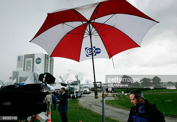 Television journalists take cover as they report on Space Shuttle Discovery July 13 2005 as storm clouds and lightning surround the Kennedy Space...