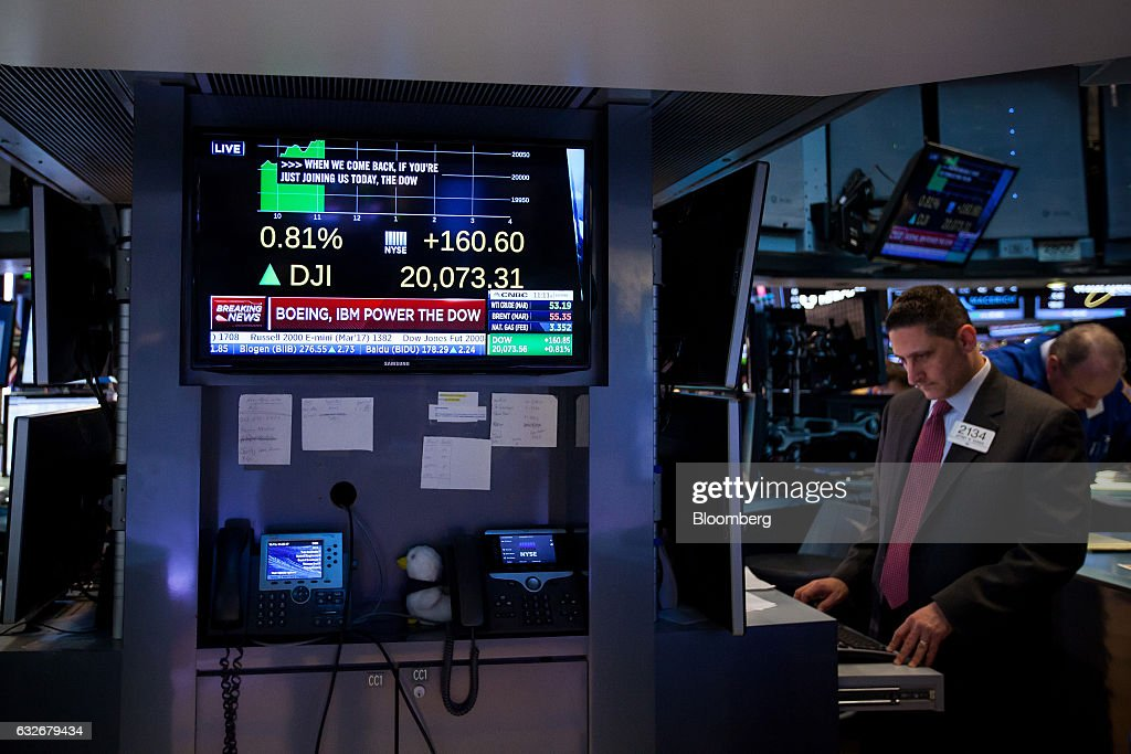 A television monitor displays news about the DOW Jones Industrial Average hitting 20,000 as a trader works on the floor of the New York Stock Exchange (NYSE) in New York, U.S., on Wednesday, Jan. 25, 2017. The Dow Jones Industrial Average climbed past 20,000 for the first time as stocks around the world extended a rally after corporate earnings reignited investors' optimism in economic growth. Bonds sold off with oil. Photographer: Michael Nagle/Bloomberg via Getty Images