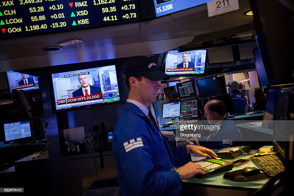 Television monitors display news about the DOW Jones Industrial Average hitting 20,000 as a trader works on the floor of the New York Stock Exchange (NYSE) in New York, U.S., on Wednesday, Jan. 25, 2017. The Dow Jones Industrial Average climbed past 20,000 for the first time as stocks around the world extended a rally after corporate earnings reignited investors' optimism in economic growth. Bonds sold off with oil. Photographer: Michael Nagle/Bloomberg via Getty Images