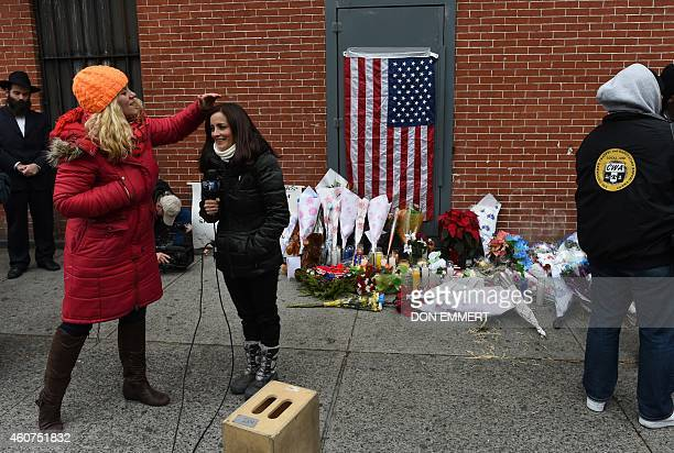 A television news crew prepares to do a report at a memorial near Tompkins Ave and Myrtle Ave December 21 2014 in New York near the site where two...