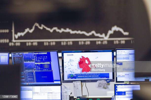 Television news report highlights a map of German coronavirus cases near the the DAX Index curve inside the Frankfurt Stock Exchange, operated by...