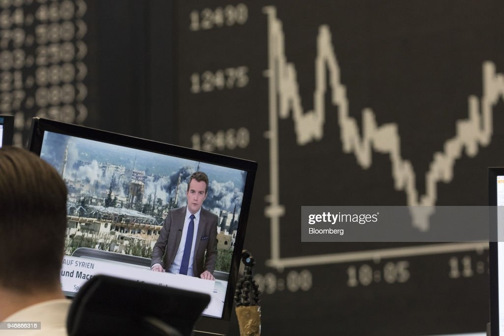 A television news report shows damage from military airstrikes on Syria as the DAX Index curve is displayed beyond at the Frankfurt Stock Exchange, operated by Deutsche Boerse AG, in Frankfurt, Germany, on Monday, April 16, 2018. Bonds declined, stocks were steady and oil fell on anticipation that the fallout from missile strikes in Syria will be limited. Photographer: Alex Kraus/Bloomberg via Getty Images