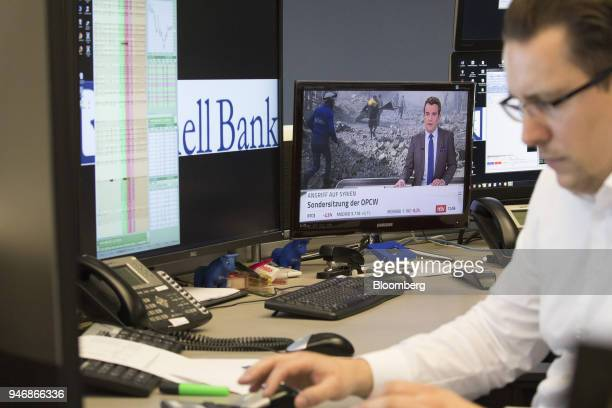 A television news report shows damage from military airstrikes on Syria as a trader monitors financial data inside the Frankfurt Stock Exchange...