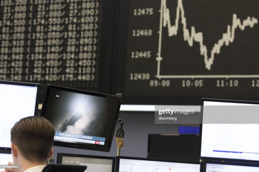 A television news report shows footage of a missile launch targeting Syria as a digital board displays the DAX Index curve beyond in the Frankfurt Stock Exchange, operated by Deutsche Boerse AG, in Frankfurt, Germany, on Monday, April 16, 2018. Bonds declined, stocks were steady and oil fell on anticipation that the fallout from missile strikes in Syria will be limited. Photographer: Alex Kraus/Bloomberg via Getty Images