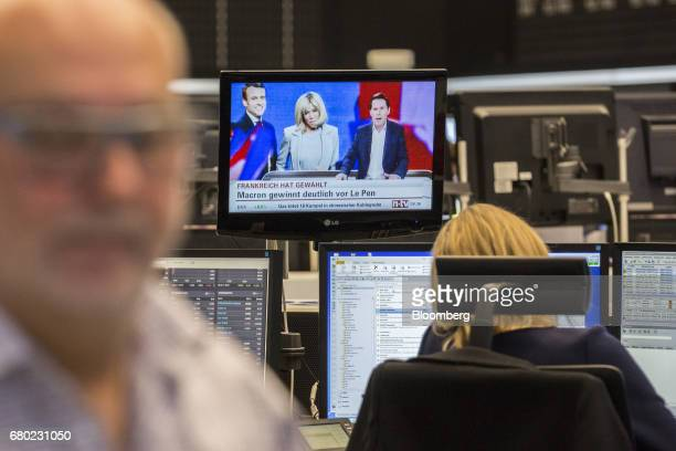 A television news report shows Presidentelect Emmanuel Macron and and his wife Brigitte Trogneux as traders monitor financial data inside the...