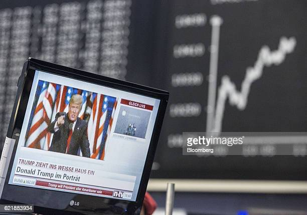 A television news report shows US Presidentelect Donald Trump as the DAX Index curve shows market reaction following the US presidential election...