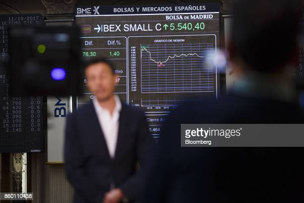 Television news reporters broadcast reports on Spanish stock prices from the Madrid Stock Exchange also known as Bolsa de Madrid in Madrid Spain on...