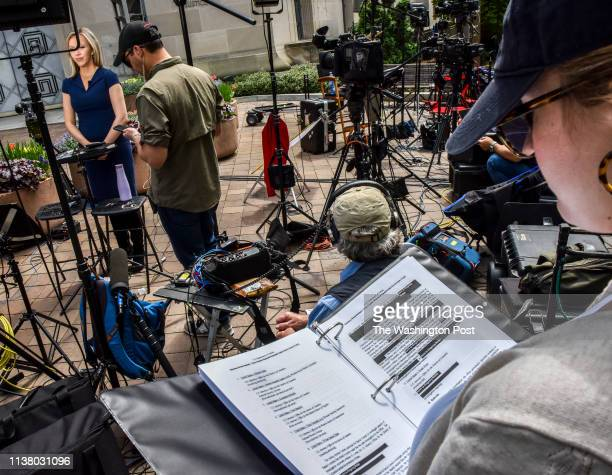 A television news team member reads a printed version of the Mueller report released this morning with redactions buy Attorney General William Barr...