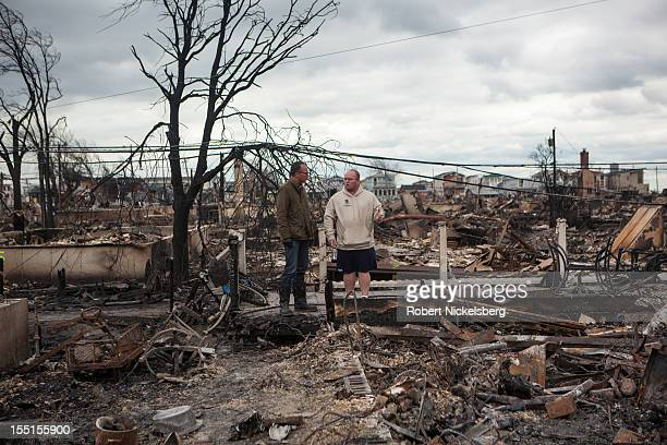 Television newscaster, Lester Holt, left, interviews Kieran Burke, right, a FDNY fire marshal and resident of Breezy Point whose home was burned...