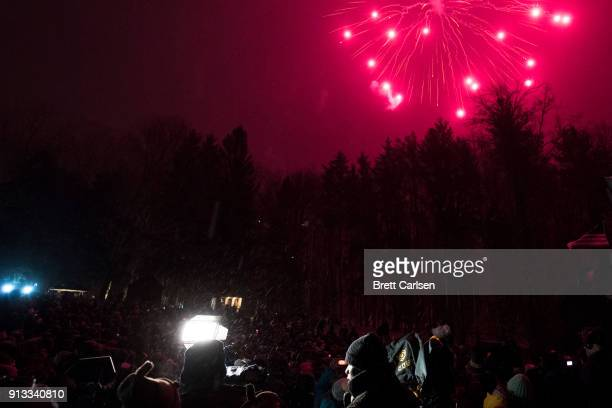 Television newspeople speak on camera as fireworks explode over the tree line during ceremonies for Groundhog Day on February 2 2018 in Punxsutawney...
