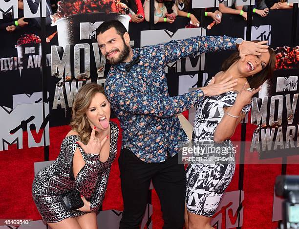 Television personalities Camila Nakagawa Frank Sweeney and Aneesa Ferreira arrive on the red carpet for the 2014 MTV Movie Awards at the Nokia...