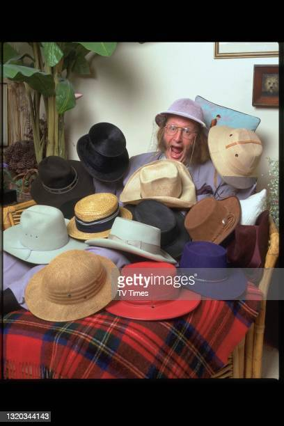 Television personality and horse racing commentator John McCririck photographed at home with a selection of hats, circa 1994.