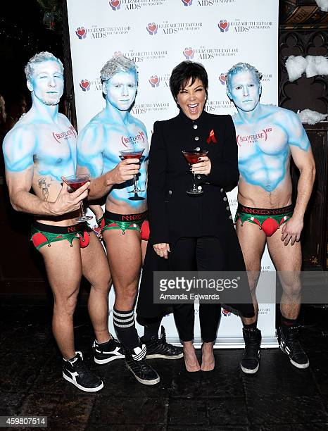 Television personality Kris Jenner poses with models while her daughter Kim Kardashian raises a toast to the Elizabeth Taylor Foundation/World AIDS...