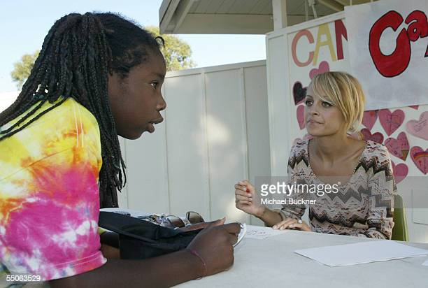 Television personality Nicole Richie greets a camper at Camp Heartland, a summer camp that serves children infected with or affected by HIV/AIDS, on...