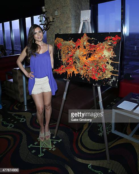 Television personality/artist Jennifer Braff stands next to an acrylic painting titled 'Molton Lava' that she painted to auction off at the VooDoo...