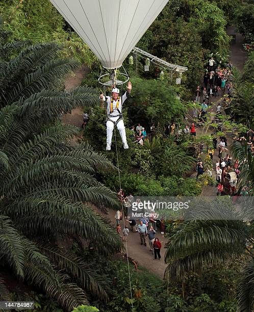 Television presenter adventurer and writer Ben Fogle waves as he takes the Olympic flame in a lantern above the tree canopy in a hot air balloon...