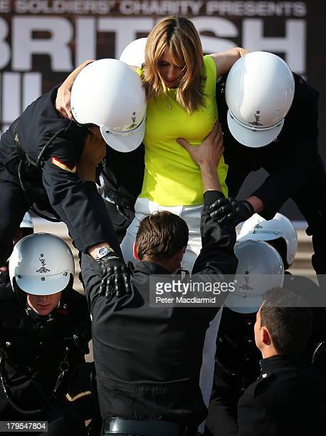 Television presenter Alex Jones is helped down by members of The Royal Signal's White Helmets display team after performing a stunt for The British...