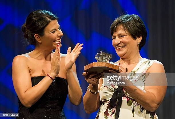 Television presenter Geppi Cucciari applaudes Roberta Bortone Riccarelli while she collects the Premio Campiello won by her late husband Ugo...