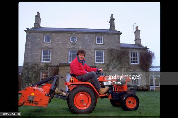 Television presenter Jeremy Clarkson, host of Jeremy Clarkson's Motorworld, driving a miniature tractor around his garden, circa January 1995.