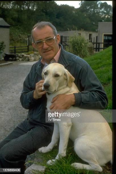 Television presenter Jim Bowen at home with his dog, circa 1989.
