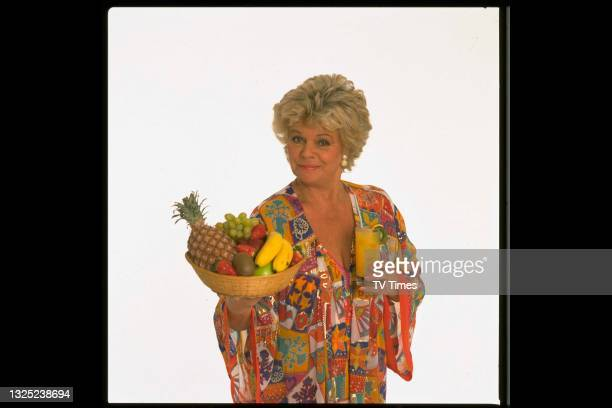 Television presenter Judith Chalmers holding a bowl of fruit and a glass of fruit juice, circa 1991.