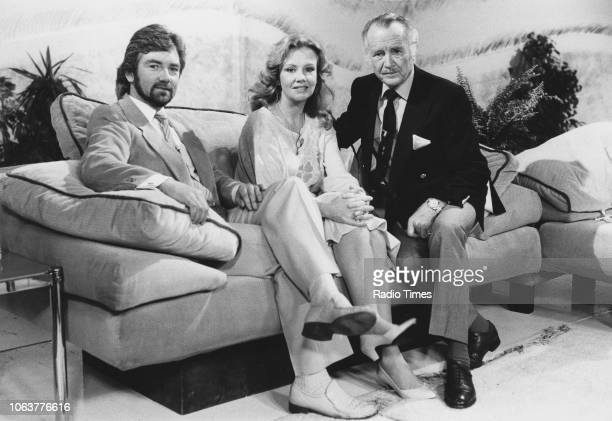 Television presenter Noel Edmonds sitting on a sofa with his guests actors Hayley Mills and Sir John Mills on the set of the show 'The Time of Your...