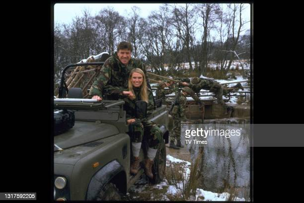 Television presenters Emlyn Hughes and Anneka Rice photographed in combat fatigues on the set of game show Combat, circa 1989.
