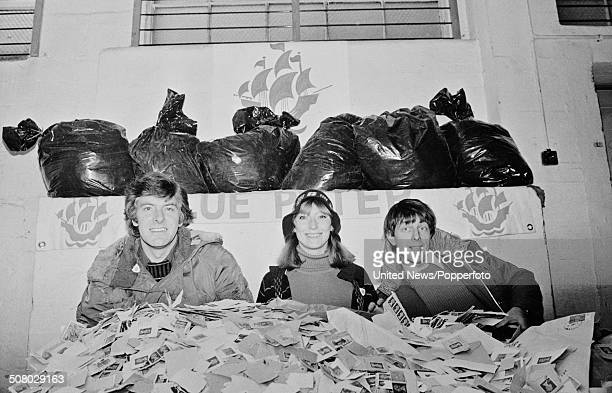 Television presenters Peter Purves Lesley Judd and John Noakes pose together with piles of used postage stamps to launch the annual Blue Peter...