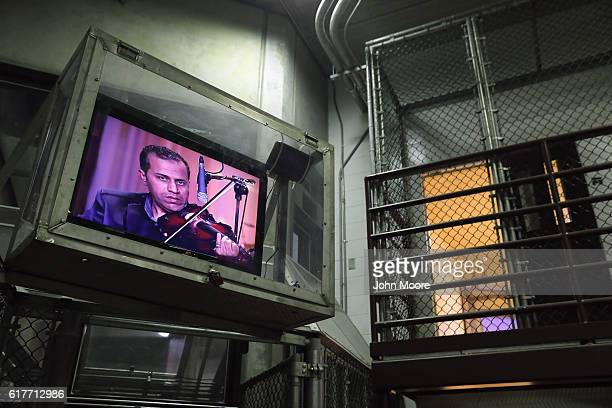A television protected by plexiglass plays an Arabic music show at the 'Gitmo' maximum security detention center on October 22 2016 at the US Naval...