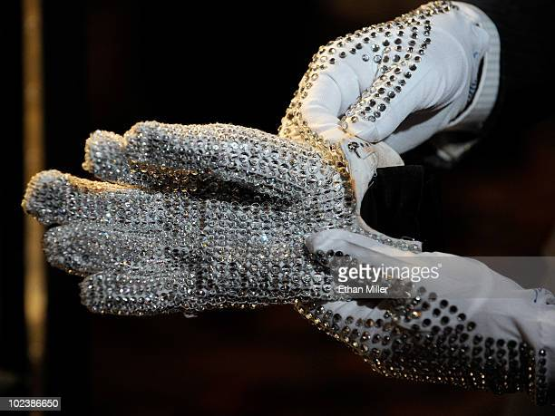 Television reporter from Japan holds a Michael Jackson Victory Tour glove covered in clear Swarovski crystals at Julien's Auctions annual summer sale...