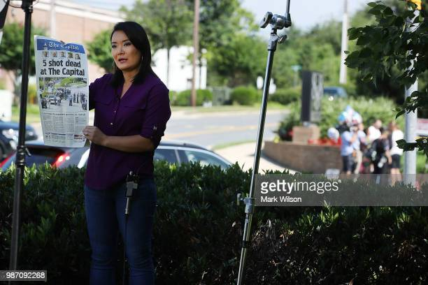Television reporter Heidi ZhouCastro holds up todays edtion of the Capital Gazette the day after 5 people were shot and killed by a gunman on June 29...