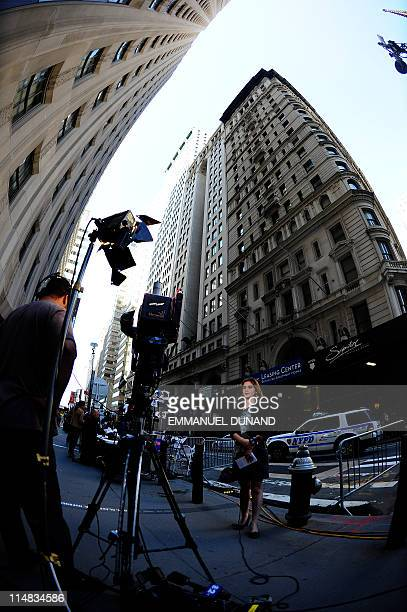 A television reporter prepares for a live report outside the building where former IMF head Dominique StraussKahn is being held under house arrest...