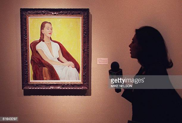 """Television reporter stands next to """"Portrait of Mrs. Carr"""" by Mexican artist Diego Rivera, during a press preview 19 November of an exhibition of..."""