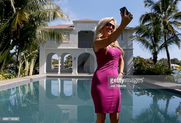 A television reporter takes a selfie in front of the pool and cabana during a tour of the former home of Al Capone on March 18 2015 in Miami Beach...