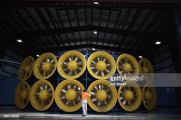 Television reporter takes pictures of the twelve fans, that create what is called a Wall of Wind, at the Florida International University engineering...
