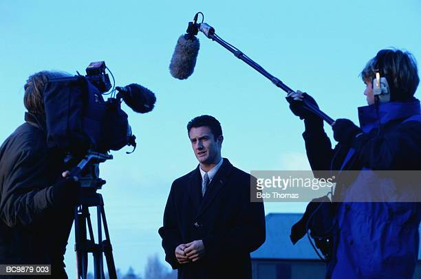 television reporter talking to camera, outdoors at dusk - journalist stock pictures, royalty-free photos & images
