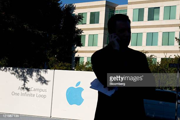 A television reporter talks on a mobile phone in front of Apple Inc signage outside the company's headquarters in Cupertino California US on...