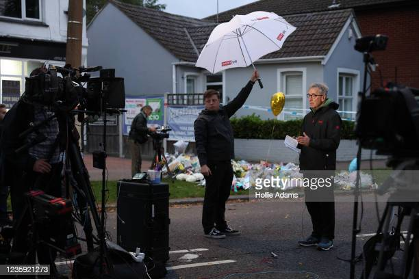 Television reporters speak in front of floral tributes laid near Belfairs Methodist Church on October 16, 2021 in Leigh-on-Sea, United Kingdom....