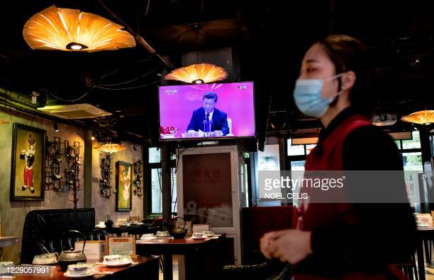 TOPSHOT A television screen at a restaurant in Beijing shows Chinese President Xi Jinping speaking during a broadcast from Shenzhen at an event...