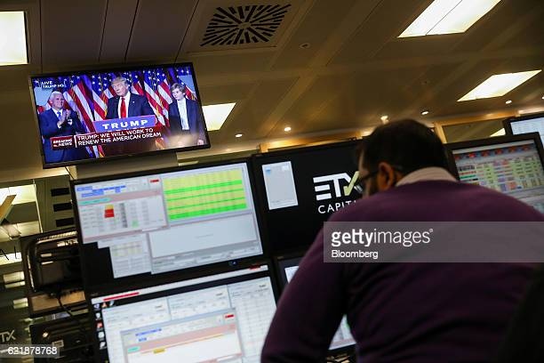 A television screen displays a news channel showing US Presidentelect Donald Trump making his victory speech as a trader monitors financial data on...
